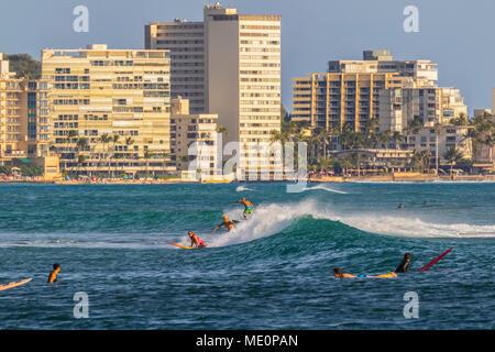 Surfing at Waikiki viewed from Magic Island, Ala Moana Beach Park; Honolulu, Oahu, Hawaii, United States of America - Stock Photo
