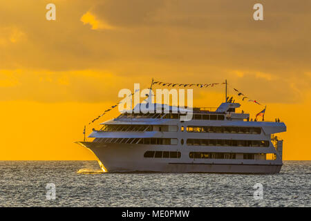 Star of Honolulu making a sunset cruise viewed from Magic Island, Ala Monana beach park; Honolulu, Oahu, Hawaii, United States of America - Stock Photo