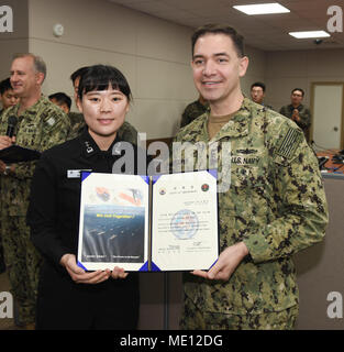 171221-N-TB148-056 BUSAN, Republic of Korea (Dec. 21, 2017) Rear Adm. Brad Cooper, commander, U.S. Naval Forces Korea (CNFK), presents Lt. Son, Hye Rim with a letter of appointment for her selection to the 'Great Young Minds' Junior Officers' Engagement and Cooperation Program. The 'Great Young Minds' initiative brings together hand-selected, young officers from the ROK and U.S. navies and challenges them to develop innovative solutions to further enhance the ROK -U.S. alliance of the future. (U.S. Navy photo by Mass Communication Specialist Seaman William Carlisle) - Stock Photo