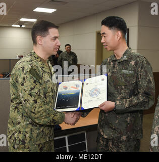171221-N-TB148-025 BUSAN, Republic of Korea (Dec. 21, 2017) Rear Adm. Brad Cooper, commander, U.S. Naval Forces Korea (CNFK), presents Lt. Cmdr. Kim, Bo Kyu with a letter of appointment for her selection to the 'Great Young Minds' Junior Officers' Engagement and Cooperation Program. The 'Great Young Minds' initiative brings together hand-selected, young officers from the ROK and U.S. navies and challenges them to develop innovative solutions to further enhance the ROK -U.S. alliance of the future. (U.S. Navy photo by Mass Communication Specialist Seaman William Carlisle) - Stock Photo