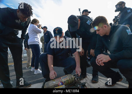 171226-N-XN518-111  SAN DIEGO (Dec. 26, 2017) Aviation Support Equipment Technician 1st Class Philip Reeve speaks to college football players from the Michigan State University Spartans about self contained breathing apparatus (SCBA) bottles on the flight deck of Wasp-class amphibious assault ship USS Essex (LHD 2) during the 2017 Holiday Bowl shipboard event. The Holiday Bowl is a post-season NCAA Division 1 Football Bowl Subdivision college football game that has been played annually since 1978 as SDCCU Stadium in San Diego. (U.S. Navy photo by Mass Communication Specialist 2nd Class Irwin S - Stock Photo
