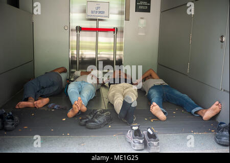 18.04.2018, Singapore, Republic of Singapore, Asia - A group of South Asian migrant workers is seen resting inside the entry of a lift. - Stock Photo