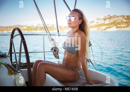Attractive woman on sailboat, travels on a luxury yacht  in Mediterranean sea along Greek islands, enjoying summer vacation - Stock Photo