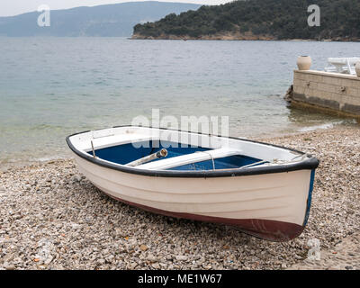 A small boat in the harbor of Valun (Island Cres, Croatia) on a cloudy day in spring - Stock Photo