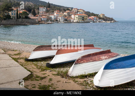 Boats lying on the beach of Valun (Island Cres, Croatia) on a cloudy day in spring - Stock Photo