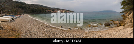 Panorama of the beach of Valun (Island Cres, Croatia) on a cloudy day in spring - Stock Photo