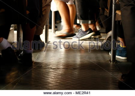 close-up of the feet of diverse passengers commuting to work and school on the local buses in the city in Thailand - Stock Photo