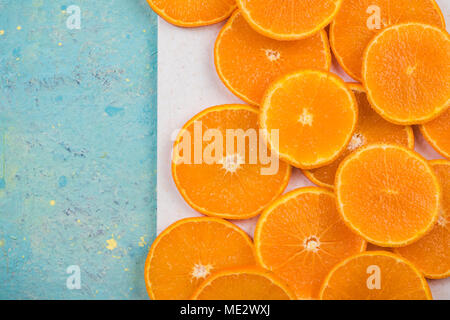 Orange slices on marble board and blue table. Vibrant food image. - Stock Photo