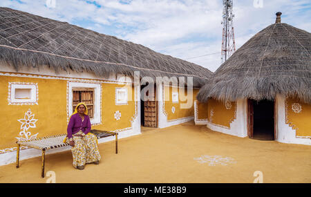 Rajasthani aged tribal woman sitting in front of a mud hut at a rural village near Thar desert Jaisalmer, India. - Stock Photo
