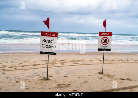Signs warning that the beach is closed due to storms and dangerous surf on the Gold Coast in Australia Stock Photo