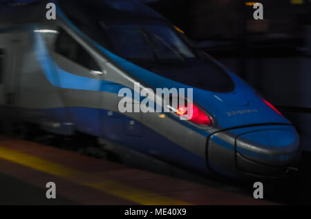 Blue locomotive of Pendolino train with red rear lights on the platform at night in Zabrze, Silesian Upland, Poland. - Stock Photo