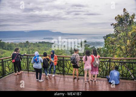 visitors enjoy the early morning mood of the Borobudur temple rising out of the mists of the Kedu Plain from elevated Punthuk Setumbu, Central Java, I - Stock Photo