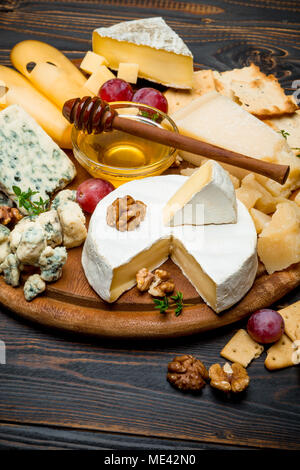 various types of cheese - brie, camembert, roquefort and cheddar on wooden board - Stock Photo