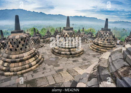 perforated stupas containing Buddha statues on the circular top terraces of 9th century Borobudur Buddhist temple, Central Java, Indonesia - Stock Photo