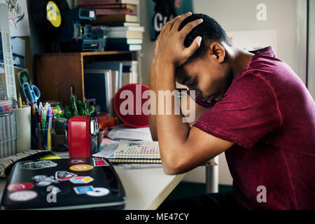 Teenage boy in a bedroom doing work stressed out and frustrated - Stock Photo