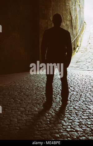 Rear view of a mysterious male figure standing on cobbled road - Stock Photo