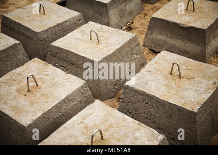 Many concrete blocks arranged in rows for a building foundation. Construction site groundwork background - Stock Photo