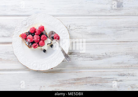 Portion cottage cheese casserole with  casserole with raspberries, blueberries and chocolate on a white plate on wooden table. health or diet concept. - Stock Photo