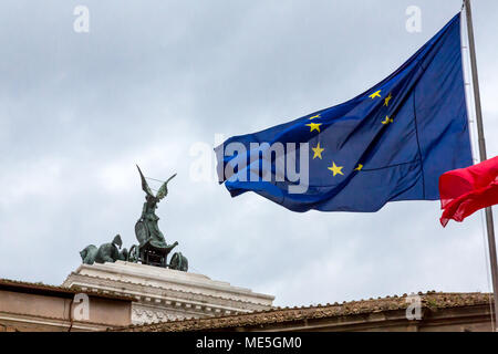 Rome, Italy - February 21, 2015: European and Italian flags fly behind the Altare Della Patria on a cloudy wet day in Rome. - Stock Photo