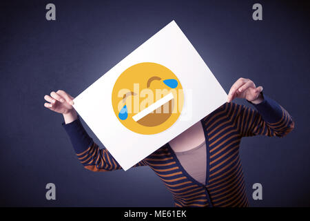 Young casual woman hiding behind a laughing emoticon on cardboard - Stock Photo