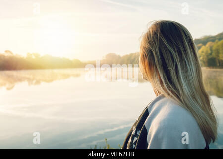 Young woman contemplating nature by the lake at sunrise, springtime, France, Europe. People travel relaxation in nature concept. Tones image - Stock Photo