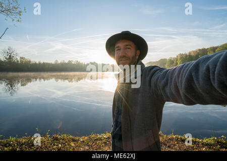 Young man by the lake at sunrise takes a selfie portrait using mobile phone, beautiful reflection on water surface. Travel people concept France - Stock Photo