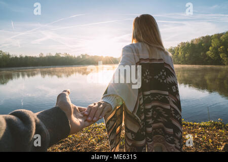 Follow me to concept, Young woman leading boyfriend to the lakeshore at sunrise, holding hands, People travel couple beginning. Shot in France, Europe - Stock Photo