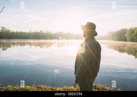 Young man contemplating nature by the lake at sunrise, springtime, France, Europe. People travel relaxation in nature concept. Toned image - Stock Photo