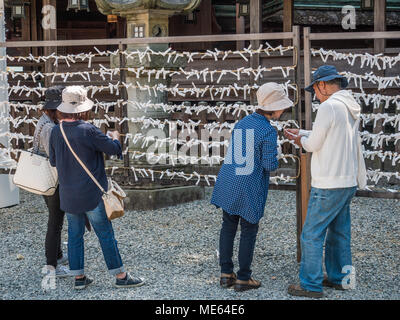 Reading omikuji, fortune telling paper strips, Konpira-san Shrine, Kotohira, Kagawa, Shikoku, Japan - Stock Photo