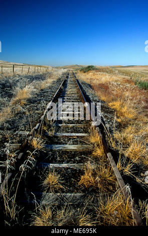 Abandoned railway tracks through a field. Cantal. Auvergne. France - Stock Photo
