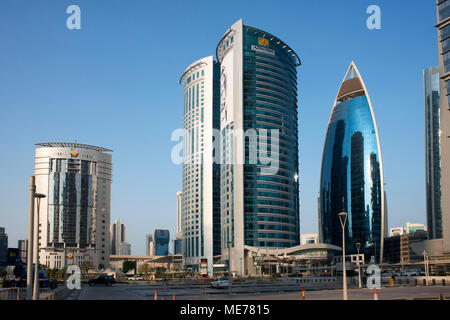 View of the Alfardan Towers twin skyscrapers located in the West Bay area of Doha covered with pictures of the ruling Al Thani emir of Qatar - Stock Photo