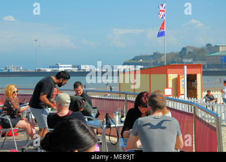 Weymouth, Dorset. 21st April 2018. People enjoy a cooling drink at a beach bar, on hot and sunny Weymouth beach Credit: stuart fretwell/Alamy Live News - Stock Photo