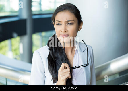 Closeup portrait, woman leader in gray suit with black glasses under chin thinking hard, cogitative, needing to make tough decisions, isolated indoors - Stock Photo