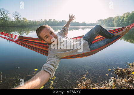 Young man takes a selfie portrait while hanging on hammock by the lake, sunset light reflecting on water surface. People relaxation communication - Stock Photo