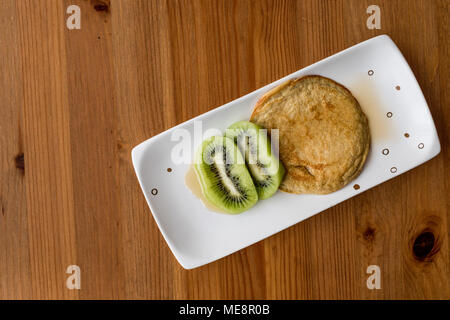 Pancake with kiwi and maple syrup (made with organic flour) copy space. homemade product. - Stock Photo