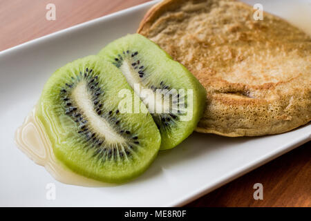 Pancake with kiwi and maple syrup (made with organic flour) homemade product. - Stock Photo
