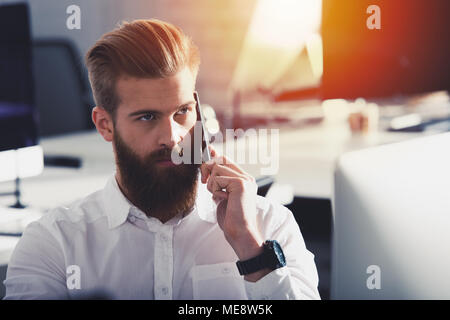 Businessman talking to the phone in office - Stock Photo