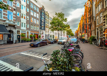 A typical Amsterdam street off the main canal area with bicycles and cars parked in front of shops in early autumn - Stock Photo
