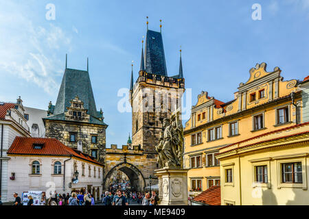 Tourists cross the Charles Bridge on the Path of the Kings leading to the lesser Tower on their way to Prague Castle. - Stock Photo