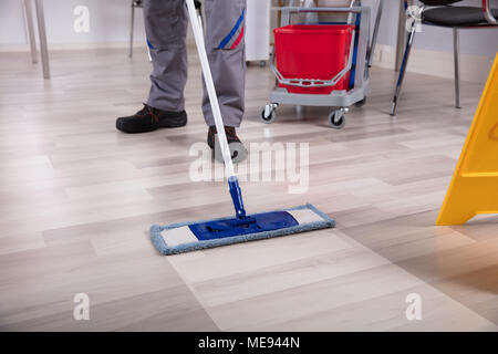 Cleaner Cleaning Hardwood Floor With Mop At Workplace - Stock Photo