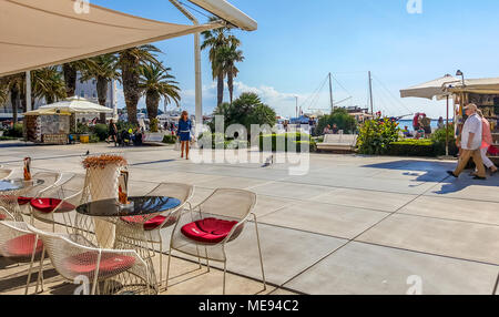 A young woman walks along the Riva Promenade at Split Harbor on the Adriatic coast as a black cat runs in front of her on the way to the pier - Stock Photo