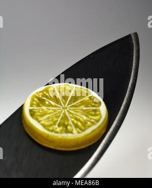 Lemon Slice on a Sharp Knife - Stock Photo