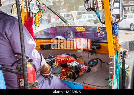 Driving in Indian traffic: View inside the colourful cab of a typical Indian tuk-tuk on the streets of New Delhi, Punjab, India - Stock Photo