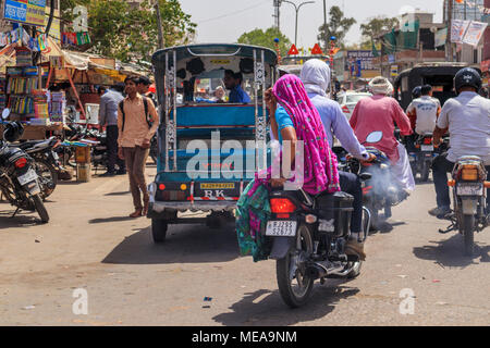 Street scene in Dausa, Rajasthan, northern India, a local woman riding pillion on a motorbike with typical colourful local veil headdress and clothing - Stock Photo