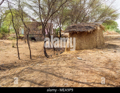 Traditional farming methods: view of typical roadside structure made of dried cow dung stored to be used for fuel, near Dausa, Rajasthan, north India - Stock Photo