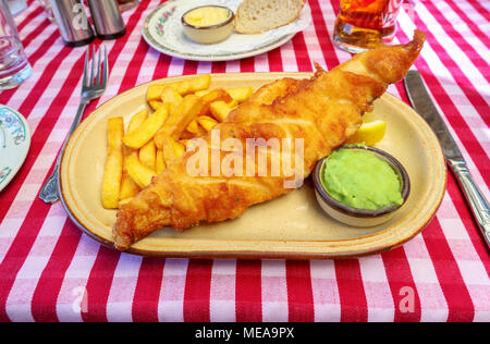 Battered fish (beer batter), golden chips, mushy peas lunch or dinner: plate of traditional British pub food on a red & white check gingham tablecloth - Stock Photo