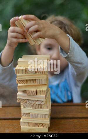 Cute child playing with building blocks and developing fine motor skills and problem solving, Townsville QLD, Australia - Stock Photo