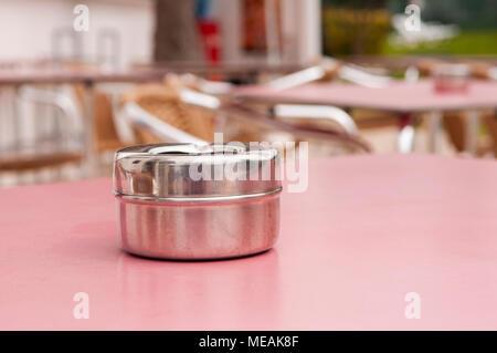 Steel ashtray on a table outside a hotel bar. - Stock Photo