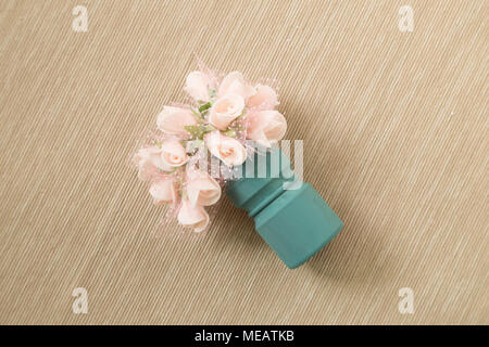 Decorative pink flower on brown fabric background - Stock Photo