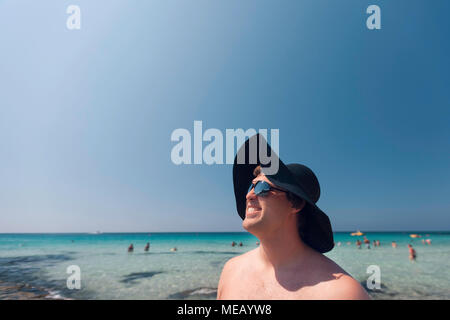 Man stood on the beach wearing straw black hat. Outdoor portrait of smiling young man on the beach. - Stock Photo